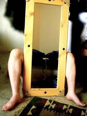 Nude man holding a full-length mirror between his knees.